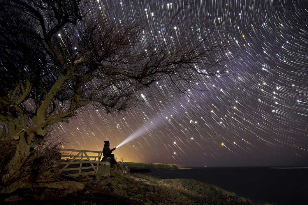 "(c) André Farinha, Portugal, Entry, Open Competition, 2015 Sony World Photography Awards ""Searching for Liife"" The picture was taken on a cold cold night. The final image is a result of 90 photos of 30 seconds exposure, each. In the final stretch of these 90 photographs, the photographer ran to the fence made of stones, sat down and pointed the flashlight ttowards the sky"
