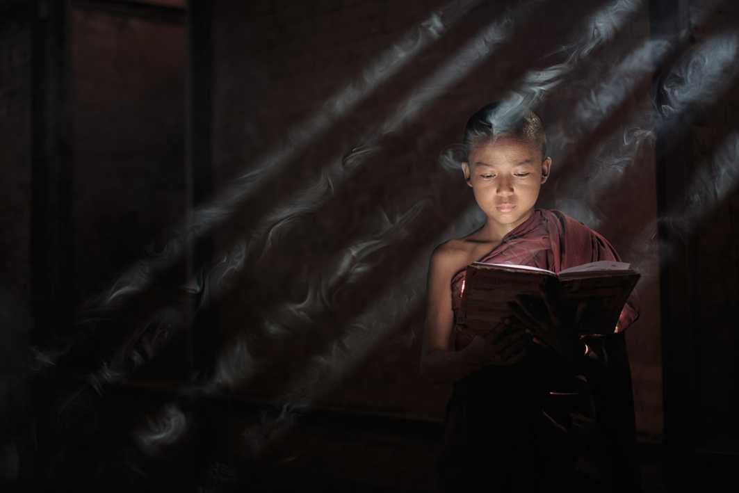 (c) Neil Herbert, UK, Entry, Open Competition, 2015 Sony World Photography Awards IMAGE DESCRIPTION: Whilst travelling in Myanmar I visited the Nat Taung Kyaung monastery in Bagan and was able to arrange a shoot with some novice monks. This is my favourite from the series as the sun was in the perfect place to beam light through the window and bounce it off the monks book illuminating his face perfectly. The incense smoke passing through the shafts of light finished the image of perfectly.